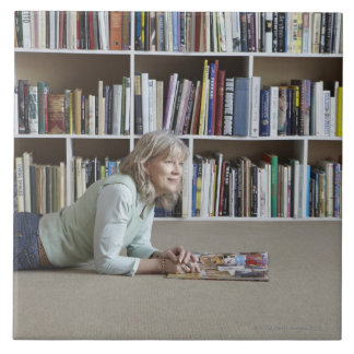 Leitura da mulher mais idosa por estantes azulejo quadrado grande