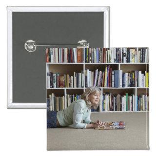Leitura da mulher mais idosa por estantes botons