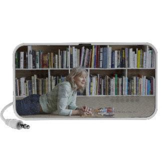Leitura da mulher mais idosa por estantes caixinhas de som para notebook