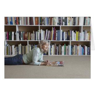 Leitura da mulher mais idosa por estantes cartão