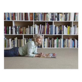Leitura da mulher mais idosa por estantes cartão postal