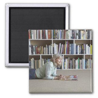 Leitura da mulher mais idosa por estantes imãs de geladeira