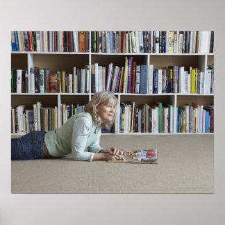 Leitura da mulher mais idosa por estantes poster