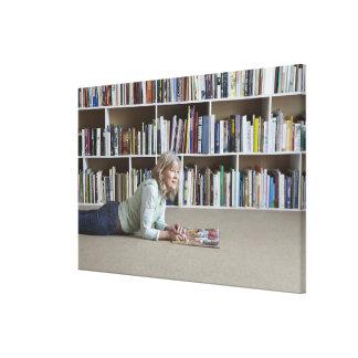 Leitura da mulher mais idosa por estantes impressão de canvas envolvidas