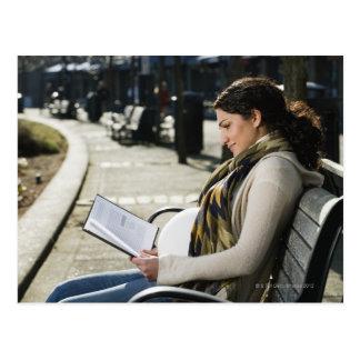 Leitura do Oriente Médio grávida da mulher no Cartão Postal