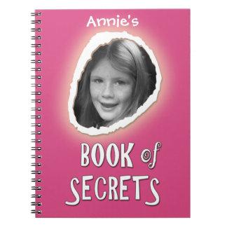 Livro cor-de-rosa dos segredos com foto feita sob cadernos