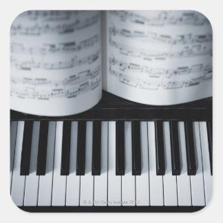 Livro das chaves e de música do piano adesivo quadrado