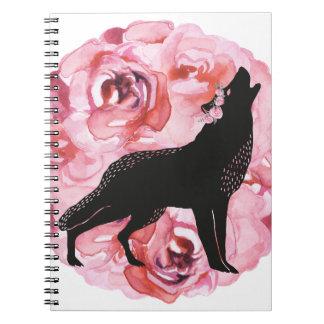 Lobo preto com o caderno cor-de-rosa do branco dos
