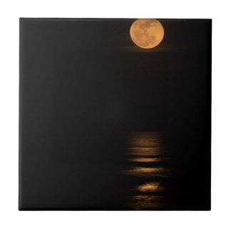 Lua cheia dourada sobre o oceano