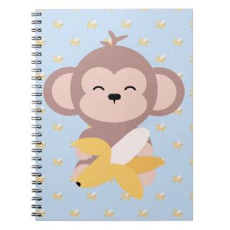 Macaco bonito de Kawaii com caderno da banana