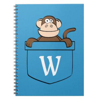 Macaco engraçado em um caderno Monogrammed do