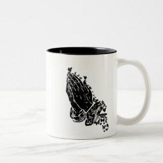 Mãos e caneca Praying das borboletas