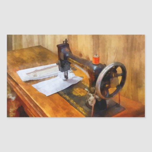 Máquina de costura com linha alaranjada adesivos em formato retangulares