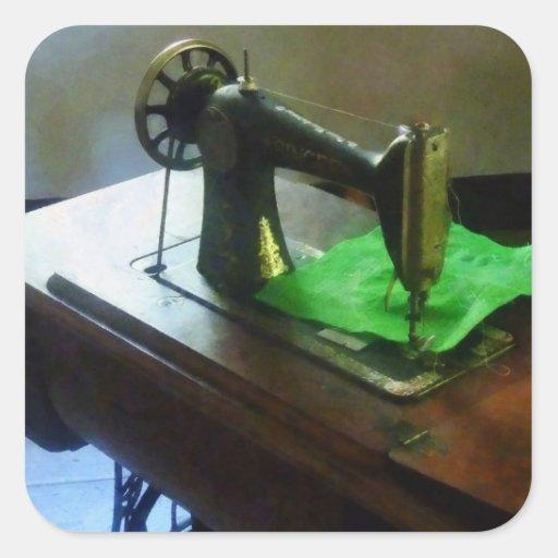 Máquina de costura com pano verde adesivo em forma quadrada