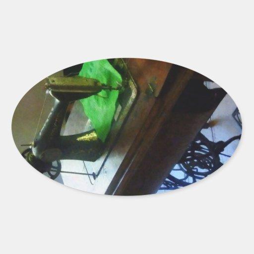 Máquina de costura com pano verde adesivos em formato ovais