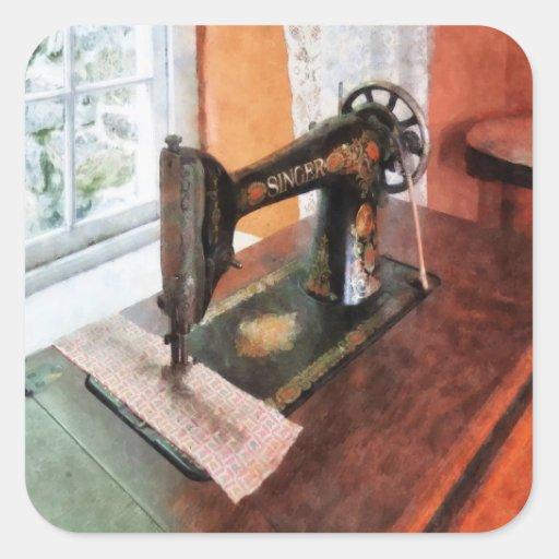 Máquina de costura perto da cortina de laço adesivos quadrados