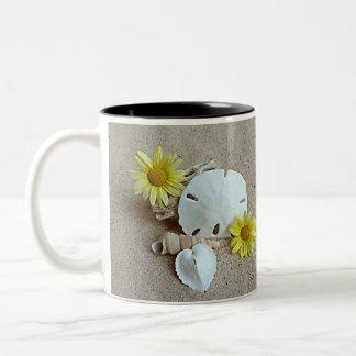 Margaridas e Seashells amarelos na caneca de café