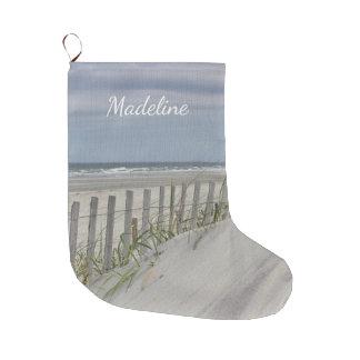 Meia De Natal Grande Dunas resistidas da cerca e de areia na praia