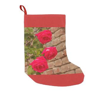 Meia De Natal Pequena os rosas escalam em uma meia do Natal da parede de