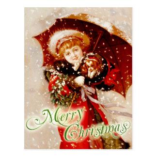 Menina e filhote de cachorro na neve do Natal Cartão Postal