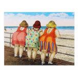 Meninas assentadas gordas do vintage na praia cartão postal