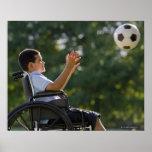 Menino latino-americano, 8, na cadeira de rodas co posters