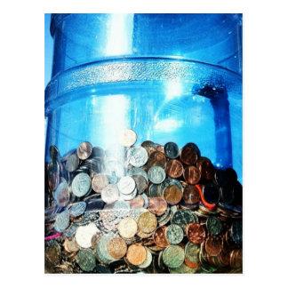 Moedas do dinheiro salvar em um cartão do jarro de