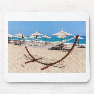 Mousepad Hammock com os guarda-chuvas de praia na costa