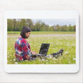 Mousepad Mulher que senta-se com o laptop no prado do
