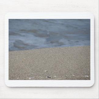 Mousepad O close up da praia da areia com mar borrou o