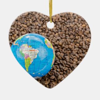 Muitos feijões de café inteiros com globo de ornamento de cerâmica