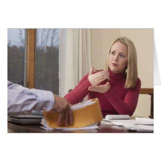 """Mulher que assina a palavra """"hipoteca"""" no cartão comemorativo"""