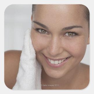 Mulher que esfrega sua cara com pano adesivo quadrado