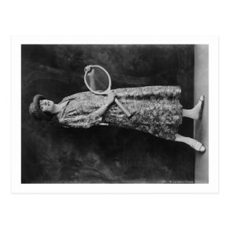 Mulher que levanta com a fotografia da raquete de cartão postal