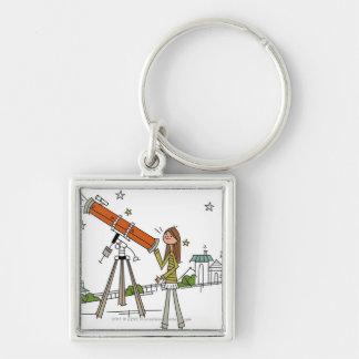 Mulher que usa um telescópio da astronomia chaveiro quadrado na cor prata