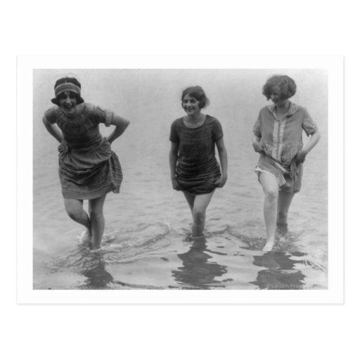 Mulheres que vadeiam na fotografia da praia de cartões postais