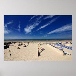 Na praia, céu azul pôster