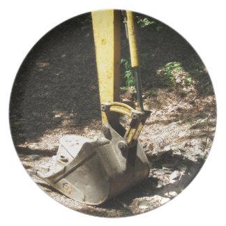 O balde da máquina escavadora amarela senta-se em prato de festa