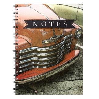 O caminhão vermelho nota o caderno espiral da foto