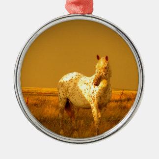 O cavalo manchado no fulgor dourado de uma ornamento de metal