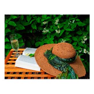 O chapéu de palha, o livro e o vinho branco em um cartão postal