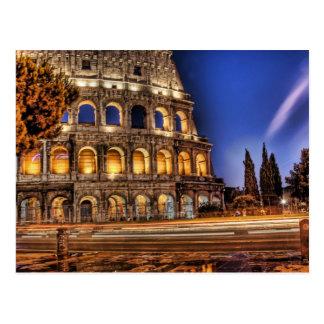 O Colosseum de Roma sob o cartão do céu nocturno