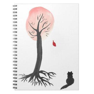 O gatinho olha a folha de queda caderno espiral