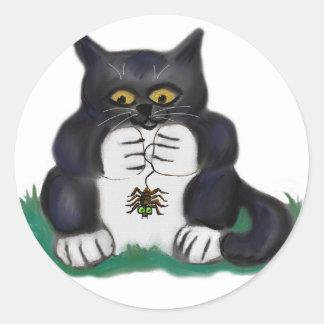 O gatinho preto do smoking encontra uma aranha de adesivo