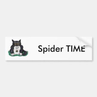 O gatinho preto do smoking encontra uma aranha de adesivo para carro