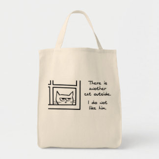 O gato irritado vê um outro gato bolsa para compras