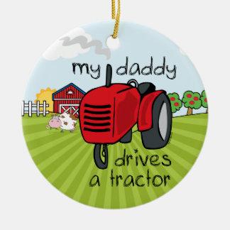 O pai conduz um ornamento da lembrança do trator