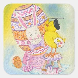 O pintinho do bebê pinta a cara do coelho no ovo adesivo quadrado