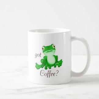 O sapo bonito de assento obteve o café? caneca de café
