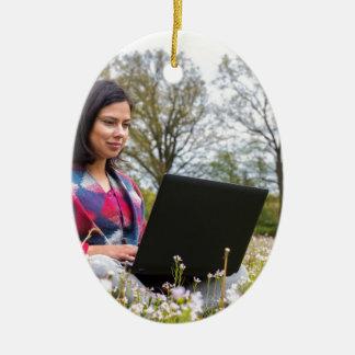 Ornamento De Cerâmica A mulher senta-se com o laptop no prado de